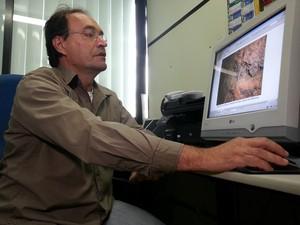 Professor José Carlos Mendonça mostra fotos tiradas dentro da galeria em 2001 (Foto: Priscilla Alves/G1)