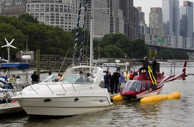 Helicóptero é rebocado pela guarda costeira após pouso de emergência no rio Hudson, em Nova York (Foto: John Minchillo/Pool/Reuters)