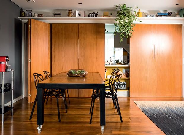 Após a reforma, que eliminou as divisões, as salas de jantar e de estar e a cozinha se conectaram em um espaço só. A cozinha pode ser fechada com a porta pantográfica de peroba rosa. Tapete da Phenicia Concept (Foto: Edu Castello/Editora Globo)