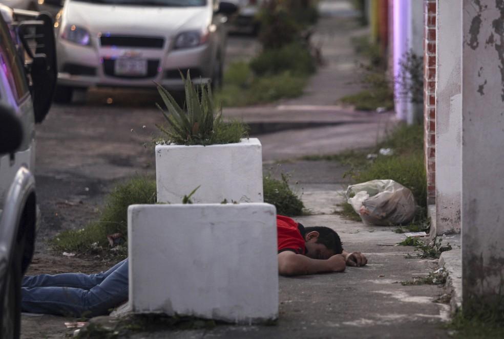 Homem jaz morto em calçada em área que foi alvo de saques na cidade portuária de Veracruz, no México (Foto: Félix Márquez/AP)