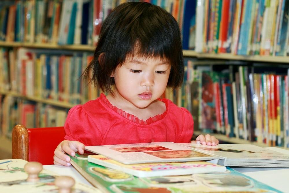 Criança lendo livros sozinha na biblioteca da escola (Foto: Shutterstock)