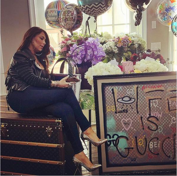 A empresária de Mariah Carey, Stella Bulochnikov, sentada em cima da mala dada pela cantora (Foto: Instagram)