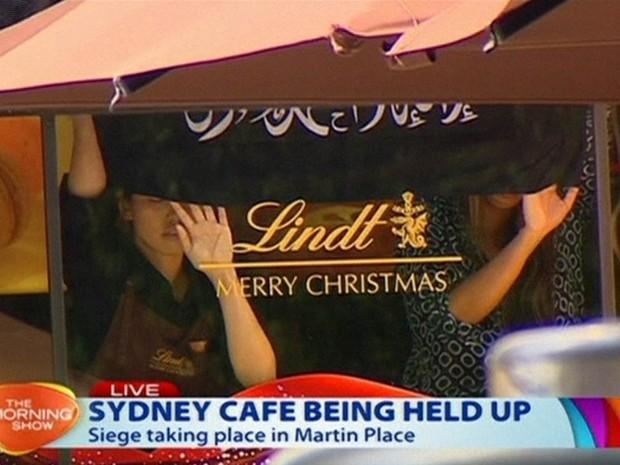 Pessoas seguram uma bandeira com escritas aparentemente árabes na vitrine da cafeteria onde um homem armado fez reféns em Sydney, na Austrália, em imagem reproduzida de uma emissora local (Foto: AP/Channel 7)