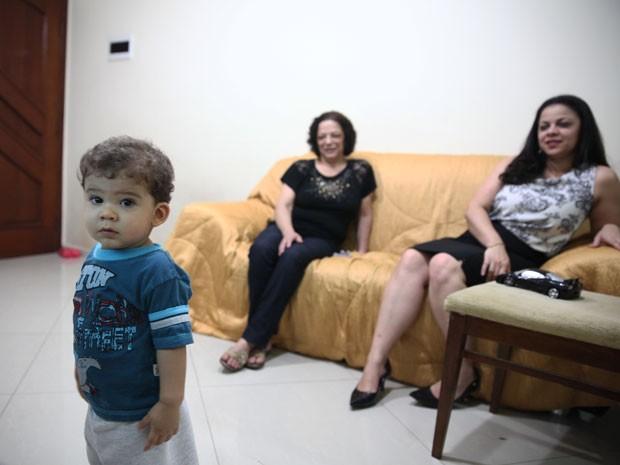 Miguel é observado pela avó Sonia e pela mãe Andreza enquanto vê televisão (Foto: Glauco Araújo/G1)