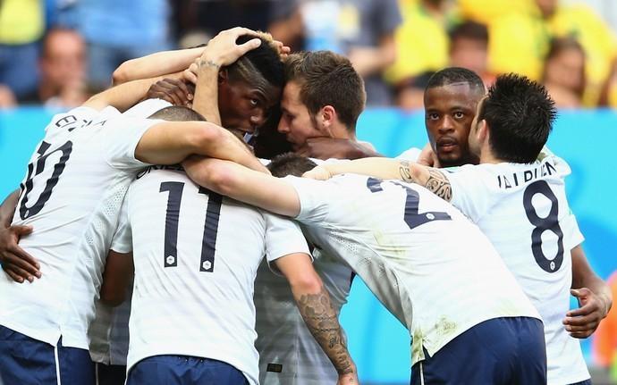 Pogba sendo abraçado pelos companheiros após marcar o primeiro gol da França contra Nigéria
