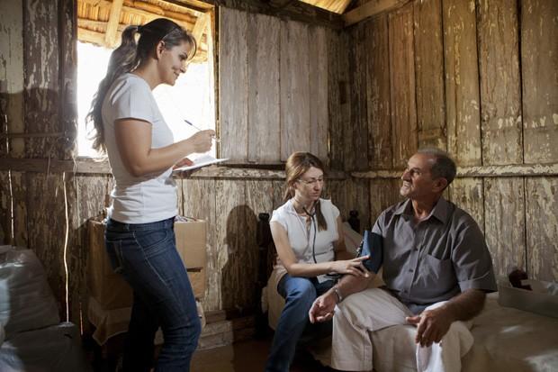 A agente de saúde Teresa (em pé) e a auxiliar de enfermagem Suselaine atendem Abelardo no sítio onde ele mora em Arco-Íris, no interior de São Paulo. (Foto: Marcelo Min)