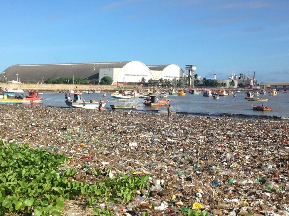 Pescadores trabalham em meio ao mar de lixo da Praia da Avenida (Foto: Natália Normande/G1)