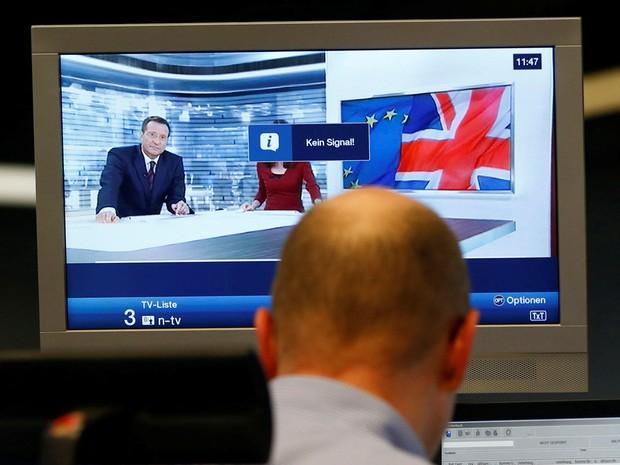 Comerciante trabalha em frente a um noticiário de uma televisão na bolsa de Frankfurt, na Alemanha (Foto: Ralph Orlowski/ Reuters)