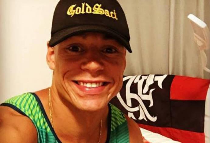 Descrição da imagem: Caio Ribeiro com a bandeira do Flamengo, seu clube de coração, ao fundo (Foto: Reprodução / Facebook)