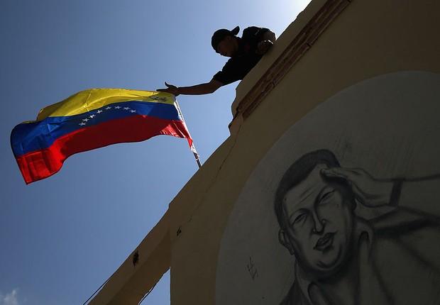 Bandeira da Venezuela sobre muro com rosto de Hugo Chávez (Foto: John Moore/Getty Images)