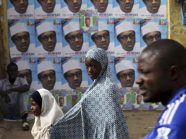 Pessoas passam por cartazes do candidato Muhammadu Buhari em Kano (Foto   REUTERS Goran 30ad00954f5aa