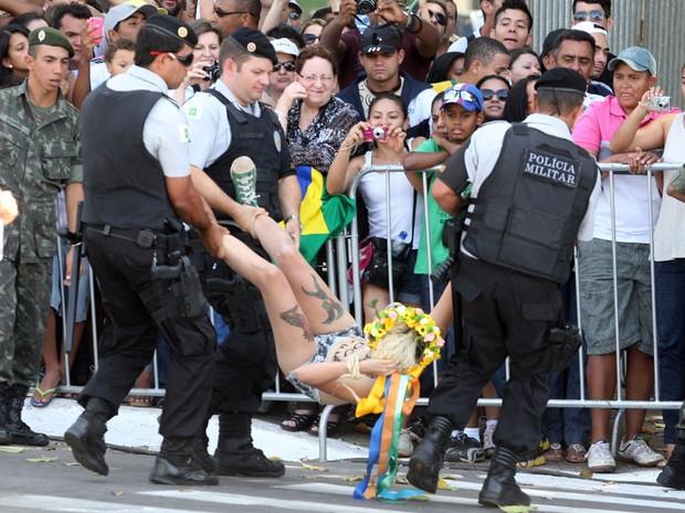 Ativista do grupo feminista Femen tira a blusa e exibe cartaz de protesto ao invadir a pista onde acontecem os desfiles de 7 de Setembro na Esplanada dos Ministérios, em Brasília. Duas ativistas foram presas. (Foto: André Dusek/AE)