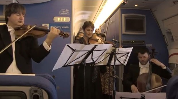 Músicos da Royal Concertgebouw Orchestra se apresentam durante voo entre Amsterdã e São Paulo (Foto: Reprodução/ Youtube/ KLM)