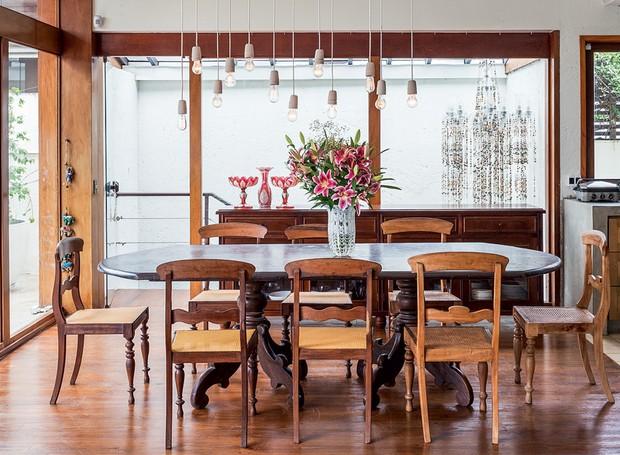 A mesa de jantar era da casa da mãe e fez parte de toda a infância de Joana. Observe o lustre ao fundo. Ele foi criado para decorar sua festa de casamento e reaproveitado ali na escada que leva ao escritório, na parte de baixo (Foto: Lufe Gomes/Life by Lufe)