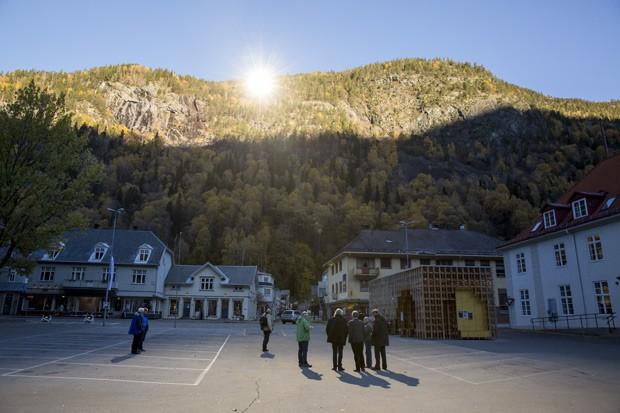 Moradores aproveitam luz solar refletida por espelhos, no centro da cidade de Rjukan. (Foto: AFP Photo / NTB scanpix / Meek, Tore)