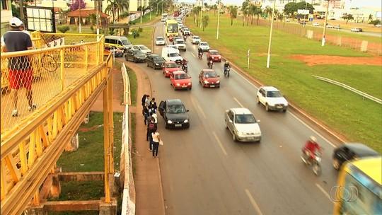 Passageiros fazem fila para entrarem em carros e vans de transporte clandestino