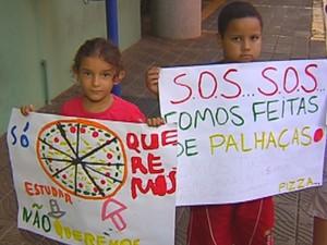 Filhos acompanham a mãe em protesto com cartazes (Foto: Reprodução / TV TEM)