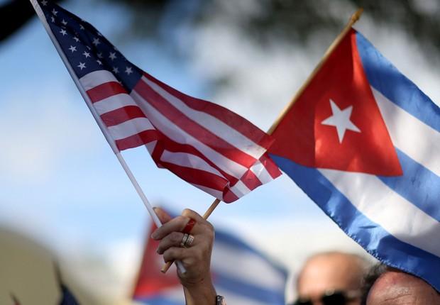 Manifestante segura bandeiras de Cuba e dos Estados Unidos (Foto: Joe Raedle/Getty Images)