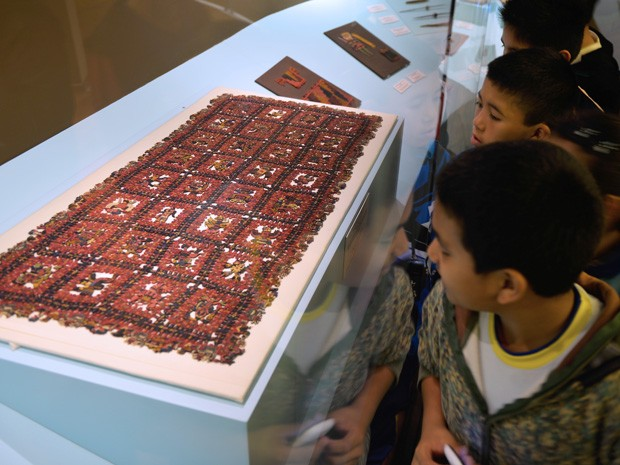 Crianças observam manto pré-inca de 2 mil anos no Museu de Arqueologia, Antropologia e História de Lima nesta sexta-feira (26) (Foto: AFP Photo/Cris Bouroncle)