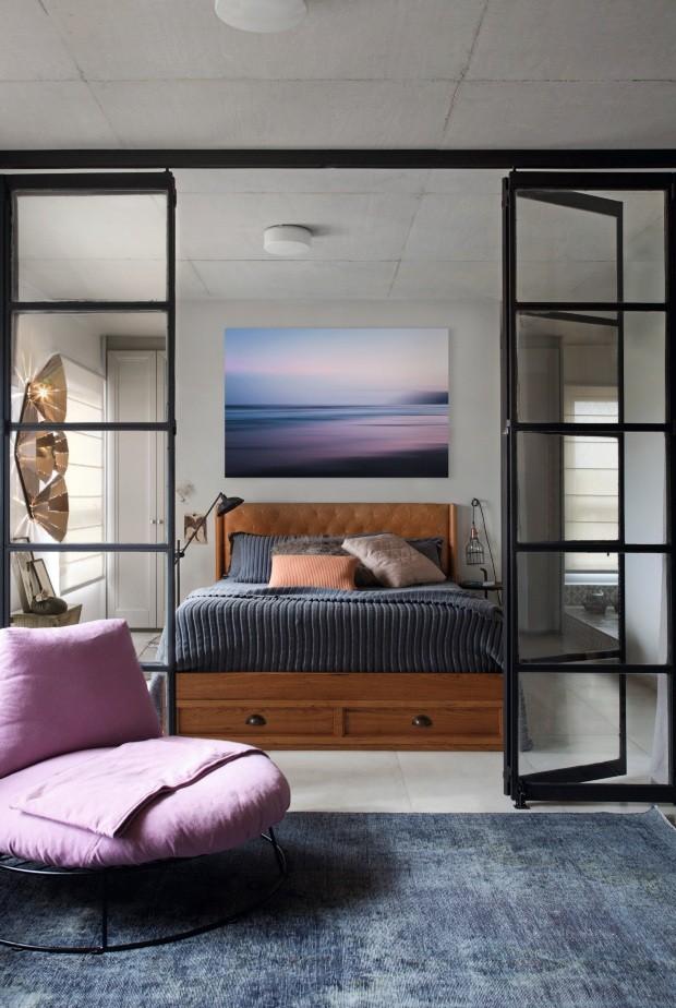 Quarto. A esquadria de aço e vidro separa sutilmente o quarto da sala. A cama tem desenho do Garimporio; acima, fotografia Mouvement 05, de Marcelo Trad, da Galerize (Foto: Marco Antonio / Editora Globo)