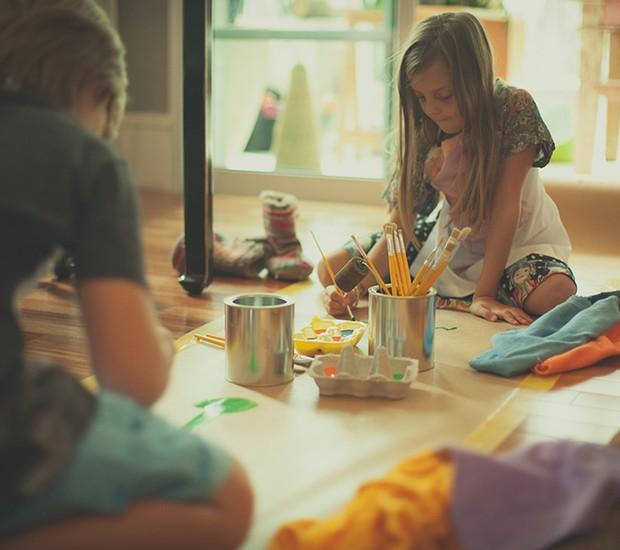 Papel kraft colado no chão com fita adesiva, latas como suporte para pincéis, caixas de ovo como paletas: o espaço para os pequenos artistas está pronto!  (Foto: Tati Abreu/Editora Globo)
