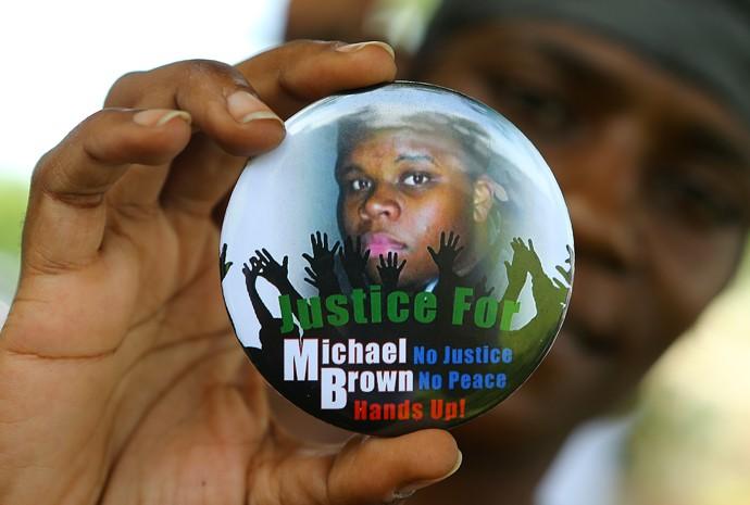 Manifestante segura botton de apoio a Michael Brown, morto por policial em Ferguson (EUA) (Foto: Atlanta Journal Constitution/AP)