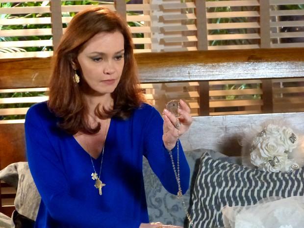 Helena fica presa ao passado e pega o cordão da fênix, aliança com Laerte (Foto: Em Família/ TV Globo)