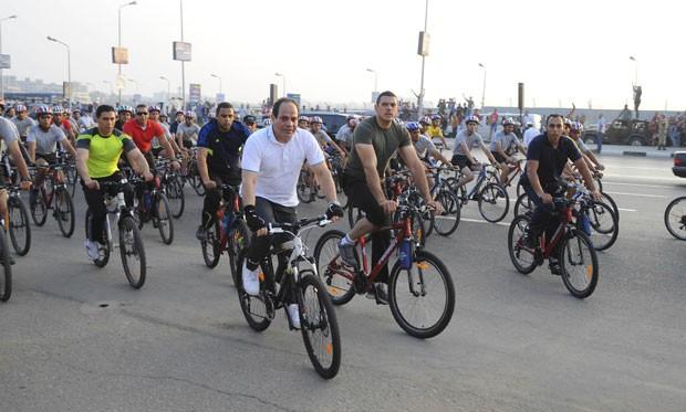 O presidente do Egito, Abdel Fattah al-Sisi (de branco) faz campanha pelo uso das bicicletas nesta sexta-feira (13) no Cairo. Objetivo é ajudar financeiramente debilitado governo a economizar dezenas de bilhões de dólares por ano em subsídios ao combustível (Foto: The Egyptian Presidency/Reuters)