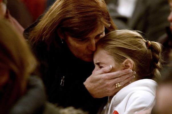Mulher consola uma garota durante vigília em Newtown nesta noite (Foto: Andrew Gombert/AP)