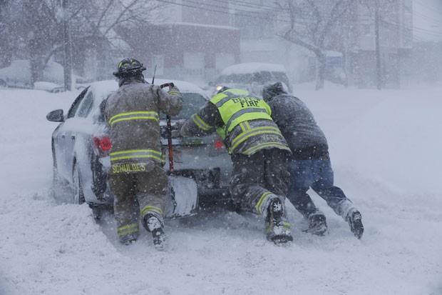 Bombeiros tentam retirar carro preso na neve em Buffalo nesta terça-feira (18) (Foto: The Buffalo News, Derek Gee/AP)