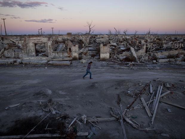 Mulher caminha por Epicuren, cidade fantasma na Argentina (Foto: Natacha Pisarenko/AP Photo)