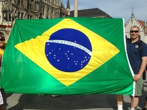 Brasileiros seguram bandeira do Brasil em Munique, nesta terça-feira (18) (Foto: Edmilson Padovani/VC no G1)
