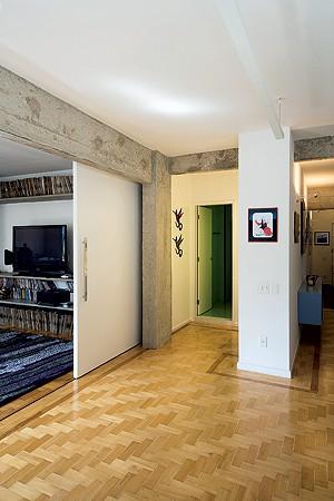 Para isolar o som do estúdio, aporta de correr com 5 m de largura tem manta de lã de vidro entre placas de MDF pintadas de branco. A estrutura de alumínio a deixa leve para ser totalmente recolhida entre a estante e a parede do banheiro social, integrando (Foto: Maíra Acayaba)