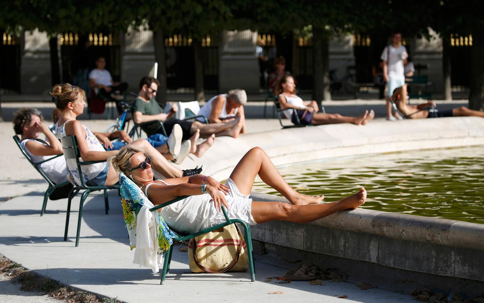 Pessoas tomam sol no jardim do Palais Royal em Paris, nesta terça-feria (13); 2016 pode ser o ano mais quente da história, segundo agência da ONU (Foto: Reuters/Charles Platiau)
