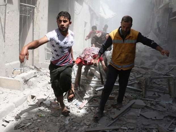 Sírios carregam desta sexta-feira (29) corpo encontrado entre destroços após ataques que atingiram Aleppo, no norte do país (Foto: Ameer Alhalbi / AFP)