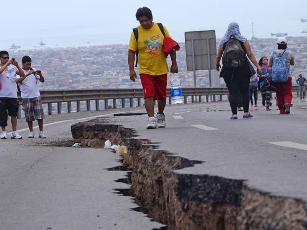 Pessoas caminham ao longo de uma estrada rachada após terremoto em Iquique, norte do Chile (Foto: Aldo Solimano/AFP)