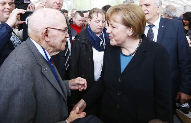 A chanceler da Alemanha, Angela Merkel, cumprimenta sobrevivente do campo de concentração de Dachau em cerimônia dos 70 anos da libertação do local neste domingo (3) (Foto: Matthias Schrader/AP)