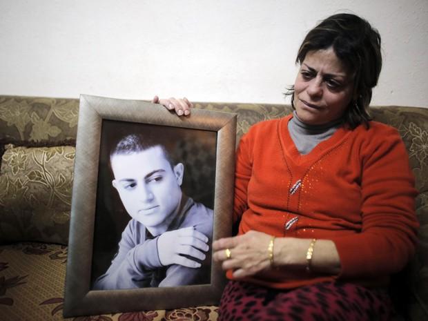 A mãe de Muhammad Musallam segura a foto de seu filho em Jerusalém, em foto de arquivo de 12 de fevereiro deste ano, antes da divulgação do vídeo que mostra o que seria a execução do jovem pelo Estado Islâmico (Foto: Ammas Awad/Reuters)