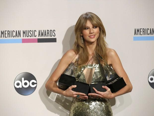 Taylor Swift posa com os quatro prêmios que fatourou no American Music Awards (Foto: Mario Anzuoni/ Reuters)