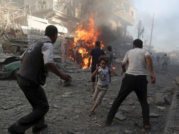 Menino corre do local de uma explosão após o que ativistas disseram ter sido um bombardeio de forças leais ao governo de Bashar al-Assad no bairro de Douma, em Damasco, capital da Síria (Foto: Bassam Khabieh/Reuters)
