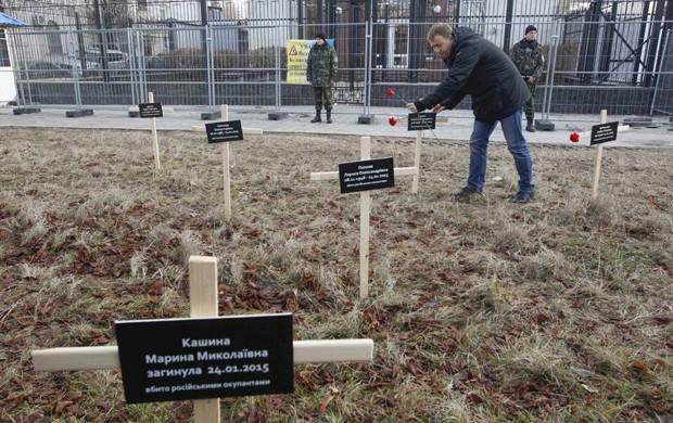 Ativista posiciona cruz com nome de vítima morta em ataque separatista durante protesto em Donetsk (Foto: Valentyn Ogirenko/Reuters)