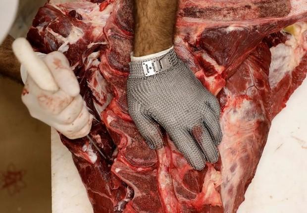 Funcionário corta pedaço de carne em um açougue em São Paulo (Foto: Paulo Whitaker/Reuters)