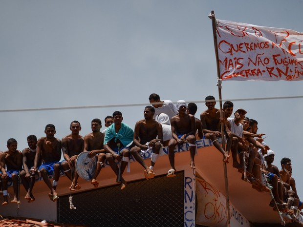 16/01: Presos são vistos no telhado com uma bandeira que traz os dizers  'Nós queremos paz, mas não fugimos da guerra' durante rebelião na penitenciária de Alcaçuz, no Rio Grande do Norte (Foto: Andressa Anholete/AFP)
