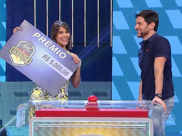 Silvia comemora com o cheque observada por Ricardo Tozzi (Foto: TV Globo)