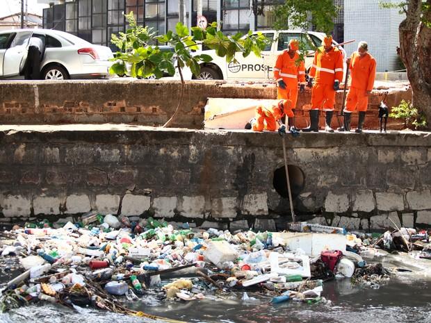 Garis tentam efetuar a limpeza do lixo trazido pela chuva. (Foto: Jonathan Lins/G1)
