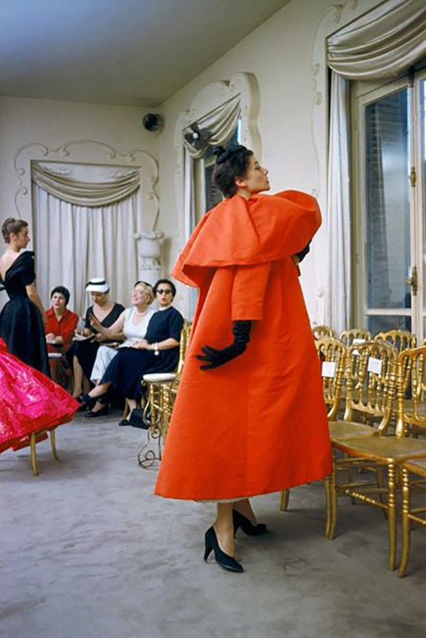 Model wearing a Balenciaga orange coat as buyers from US department store I. Magnin inspect a dinner outfit in the background. Paris, France, 1954 (Foto: © MARK SHAW, MPTVIMAGES.COM)