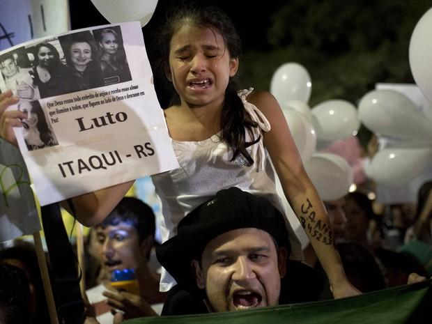 Com um cartaz mostrando fotos de vítimas do incêndio, menina chora sobre os ombros do pai em Santa Maria (RS).  Vestidas de branco, cerca de 10 mil pessoas voltaram a se reunir na Praça Saldanha Marinho, na noite de segunda-feira (28). (Foto: Felipe Dana/AP)