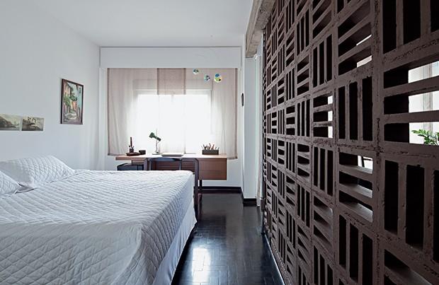 Quarto | Assentados com argamassa em posições alternadas, os cobogós de concreto, pintados com tinta cor tronco de sândalo 70YR 09/086, da Coral, filtram a luz natural que entra pela varanda. Roupa de cama da Zelo (Foto: Maíra Acayaba)