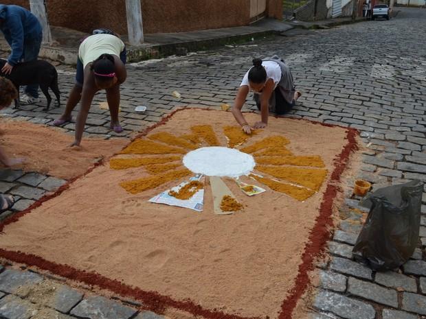 Fiéis montam tapete com serragem para celebrar Corpus Christi em Campanha, MG (Foto: Tiago Campos / G1)