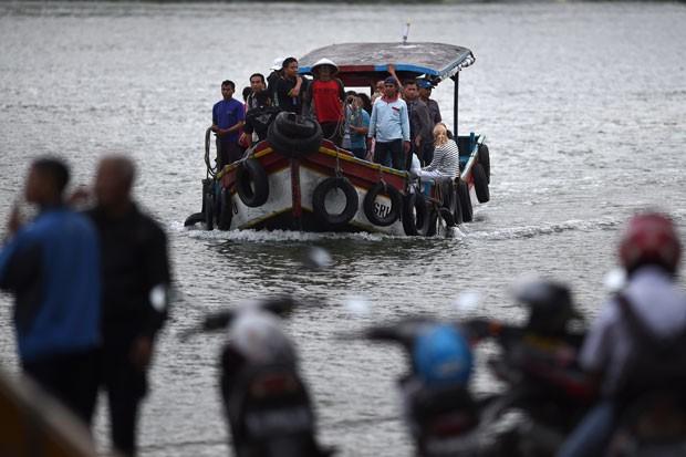 Barco com familiares de australianos no corredor da morte chega à ilha onde execuções serão realizadas na Indonésia nesta segunda-feira (27) (Foto: Romeo Gacad/AFP)